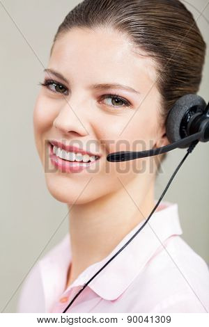 Closeup portrait of smiling customer service representative using headset at office