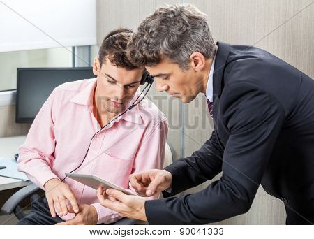 Manager and male customer service agent using digital tablet together in office