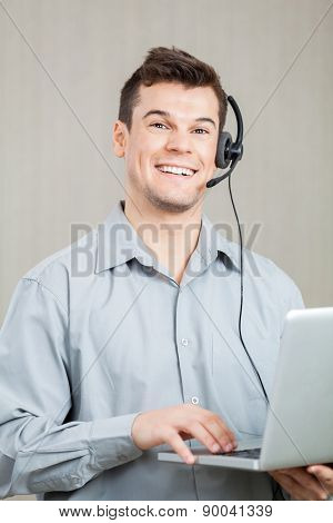 Portrait of happy male call center employee using laptop at office