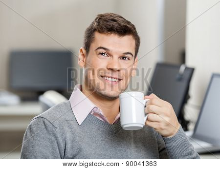 Smiling male employee having coffee in call center