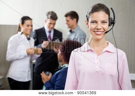 Portrait of beautiful customer service representative standing at office while team discussing in background