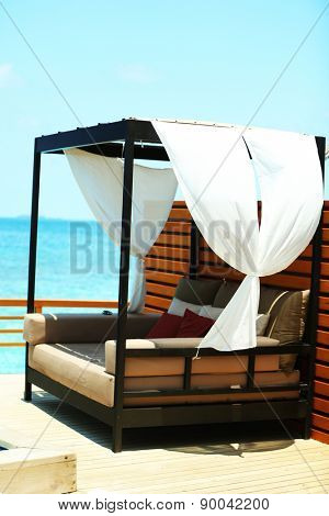 Comfortable sofa near swimming pool in resort over blue sky background