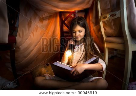 Cute Girl Reading Book In Self-made House With Flashlight