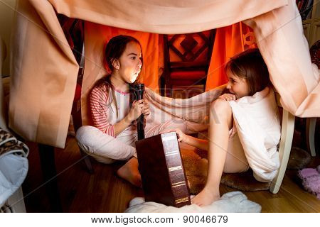 Sisters Telling Scary Stories Under Blanket At Night