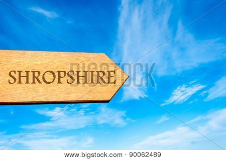 Wooden arrow sign pointing destination SHROPSHIRE ENGLAND against clear blue sky with copy space available. Travel destination conceptual image poster