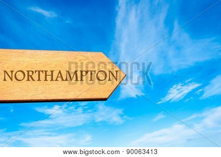 Wooden arrow sign pointing destination NORTHAMPTON ENGLAND against clear blue sky with copy space available. Travel destination conceptual image poster