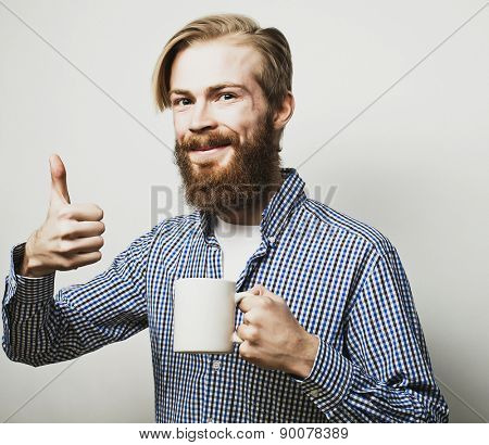 life style, happiness and people concept: young bearded man with a cup of coffee in hand and showing okey, against grey background.