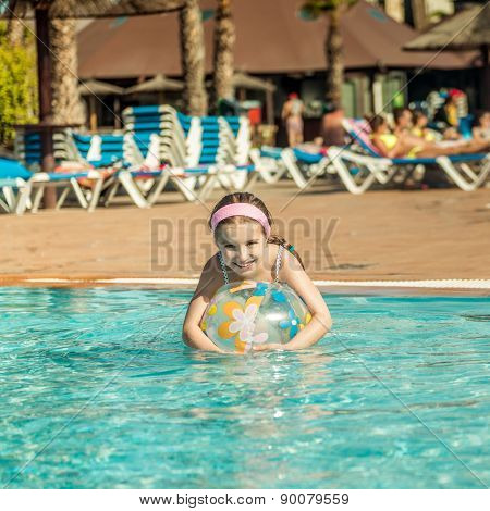 cute little girl playing in the pool with colorful ball