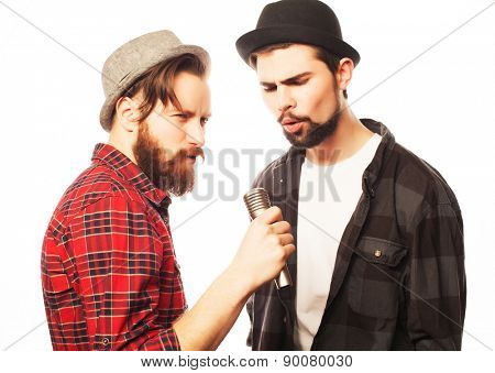 Hipsters: two young mens singing with microphone. Isolated on white.
