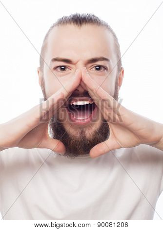 life style and people concept: Good news! Young bearded man holding hand near mouth and shouting while standing against white background.