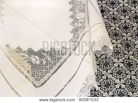 A White Tablecloth With A Lace Pattern And An Embroidered Blanket.