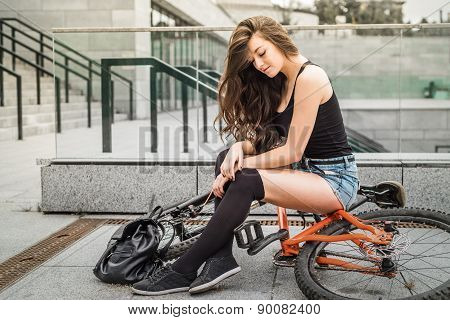 Colorful outdoor portrait of young pretty fashion model with bike.