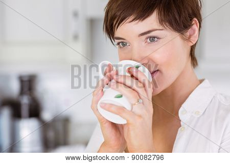 Pregnant woman having a hot drink at home in the kitchen