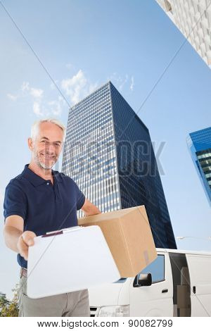 Happy delivery man holding cardboard box and clipboard against skyscraper