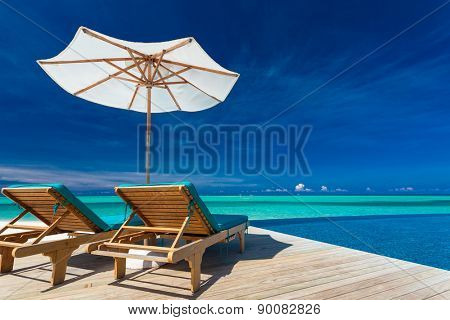 Deck chairs with umbrella overlooking infinity pool and tropical lagoon