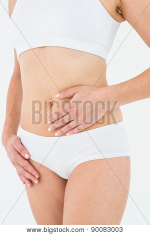 Fit woman with stomach pain on white background