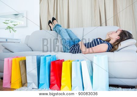 Pretty woman lying on couch near shopping bags in living room
