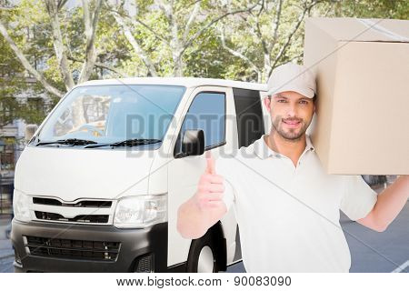 Delivery man with cardboard box gesturing thumbs up against schoolbus on ny street