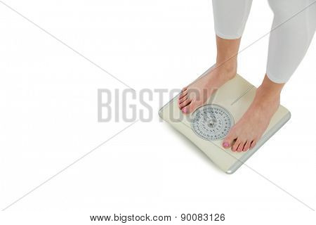 Woman standing on scales on white background