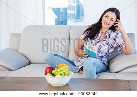 Pretty brunette looking at camera and reading a book on couch at home