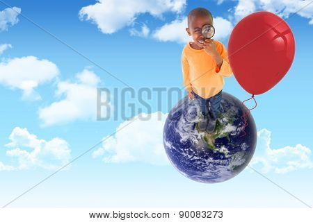 Cute boy looking through a magnifying glass against blue sky