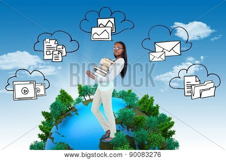 Side view of young woman carrying a pile of books against blue sky