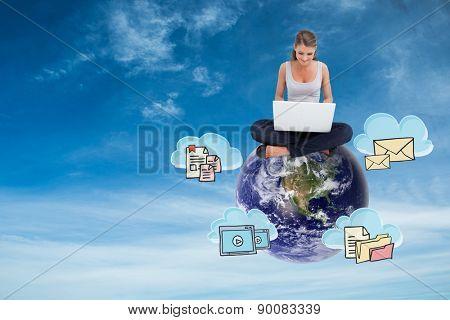 Cross-legged woman using a laptop against blue sky