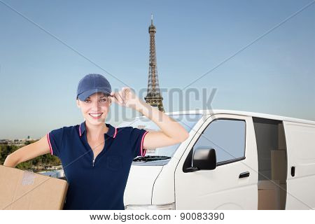 Happy delivery woman holding cardboard box against eiffel tower