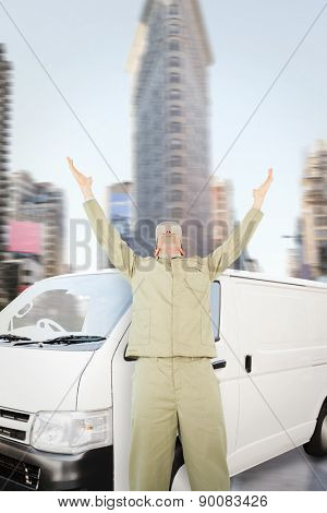 Excited delivery man with arms raised looking up against new york street