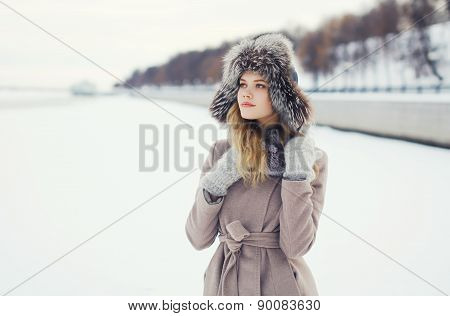 Portrait Of A Beautiful Woman Dressed A Coat And Fur Hat In The Winter Field