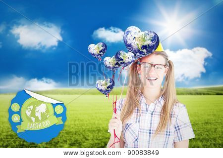 Geeky hipster smiling at camera and holding red balloons against sunny green landscape