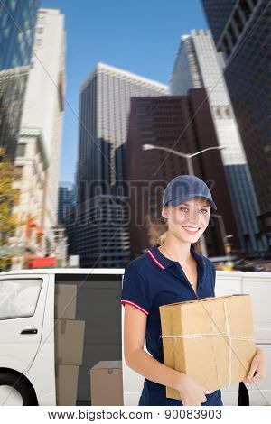 Happy delivery woman holding cardboard box against new york