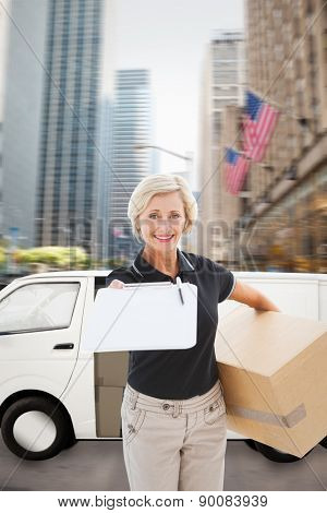 Happy delivery woman looking for signature against new york street