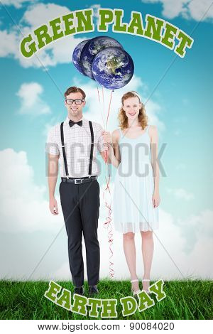 Geeky hipster couple hands in hands looking at camera against blue sky