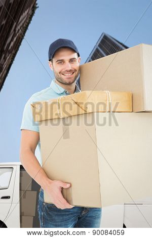 Happy delivery man carrying cardboard boxes against skyscraper