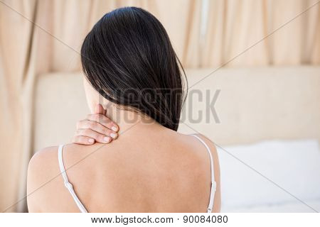 Pretty brunette with neck pain on bed at home
