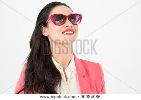 Smiling brunette wearing sun glasses on white background
