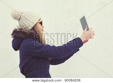Pretty Young Hipster Girl Makes Selfie On Tablet Pc Outdoors Against White Background In The City