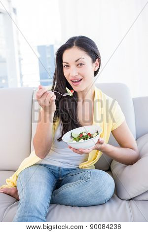 Pretty brunette looking at camera and eating salad on couch at home