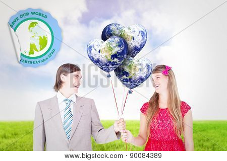 Smiling geeky couple holding red balloons against blue sky over green field