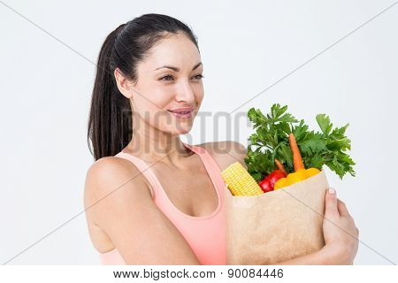 Slim woman holding bag with healthy food on white background