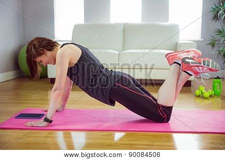 Fit woman doing press up on mat at home in the living-room