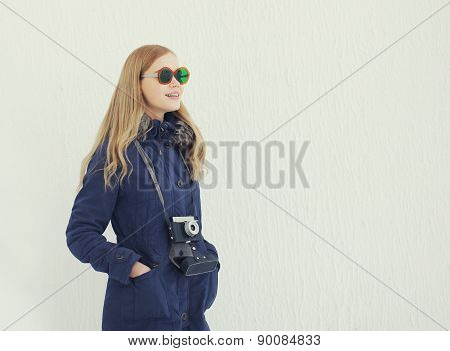 Stylish Woman In Sunglasses With Vintage Retro Camera Outdoors Against The White Wall