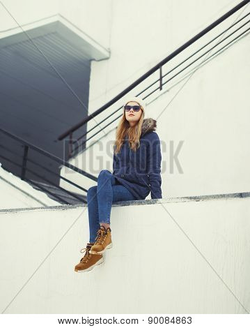 Urban Stylish Hipster Woman Outdoors Sitting In The City
