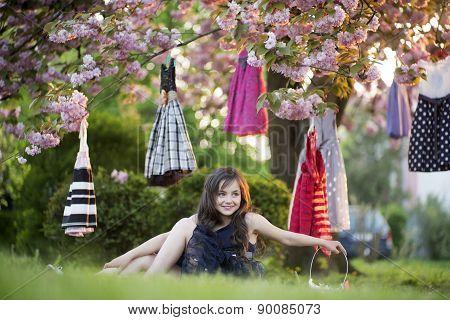 Smiling Girl Sitting In The Garden