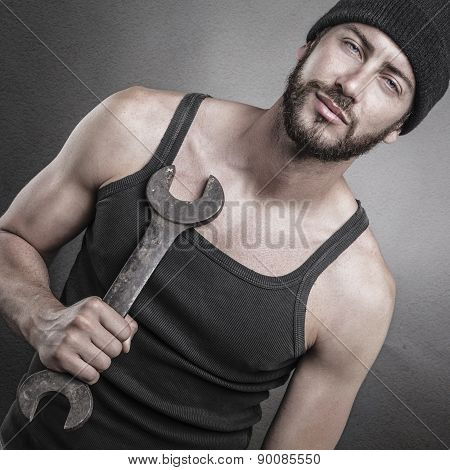 Handsome Man Standing And Holding A Wrench