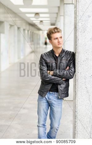 Attractive blond young man standing outside against pillar