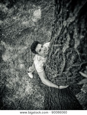 Smiling young man hugging a tree, looking up