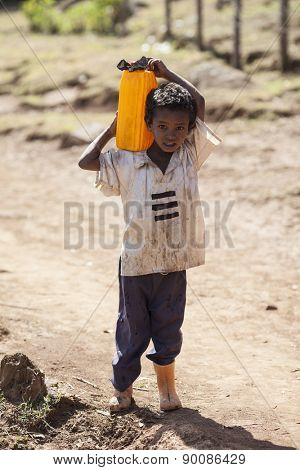 OROMIA, ETHIOPIA-APRIL 21, 2015: Unidentified child carries water from a source to his home in Oromia, Ethiopia
