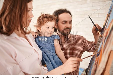 Young couple showing their little daughter how to paint